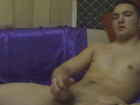 Handsome young twink is sitting on couch and hotly jerking off his dick
