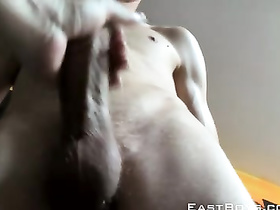 Scrawny twink is lying on the bed and pleasuring hot handjob